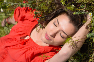 Close portrait of beautiful young woman lying on green grass