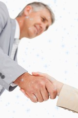 Composite image of low angleshot of a hand shake