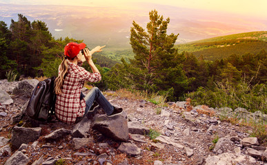 Woman climber with binocular looking at geen hills landscape