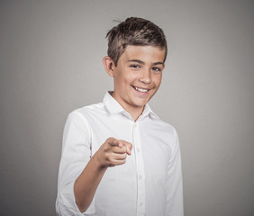 Teenager laughing, pointing finger at someone, grey background