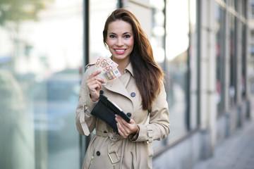 Frau mit Geld beim Shoppen
