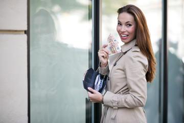 junge Frau mit Geld beim Shoppen