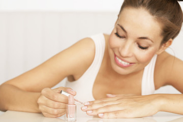 junge Frau lackiert ihre Nägel