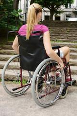 Frau mit Behinderung vor Treppe als Hindernis