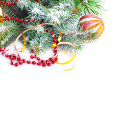 Christmas tree branch with gold serpentine and red sphere on whi