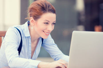 Happy woman working on computer laptop browsing internet