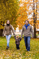Young family walks with small son in autumn park