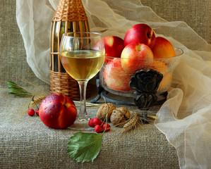 Glass of white wine, nectarines and walnuts.