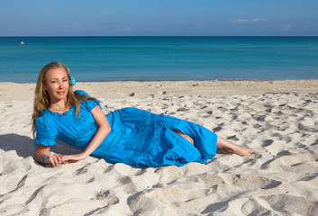 young woman in a romantic dress lies on sand near the sea,Cuba