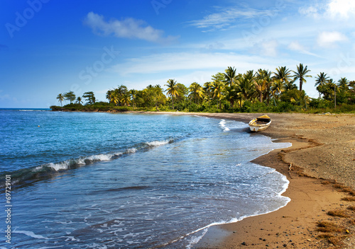 Fotobehang Kust Jamaica. A national boat on sandy coast of a bay
