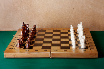 Wooden chess board with figures on green table and old wall