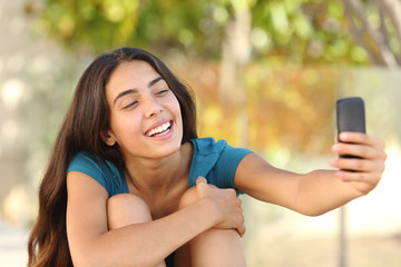 Happy teen girl taking a selfie portrait with her smart phone