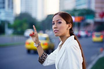 latina businesswoman calling taxi car leaving work