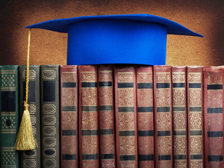 Graduation mortarboard on top of stack of books on abstract back