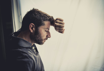 attractive man leaning on window suffering depression