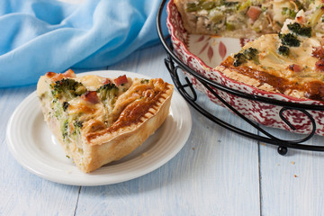 quiche with ham and broccoli on a wooden table