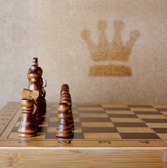 Wooden chess board with figures on table and old wall