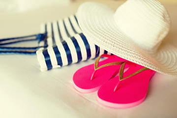 close-up of beach bag, hat and flip-flops on bed