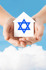 close up of hands holding house with star of david