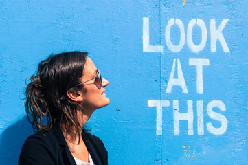"Portrait of a model next to a blue wall with ""Look at this"""