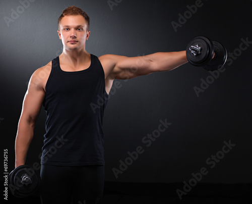 canvas print picture Fit muscular man exercising with dumbbell