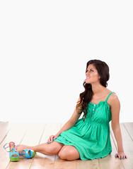 Portrait of beautiful woman is sitting on floor in green dress