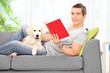 Man reading book and lying on sofa with a dog