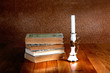 Old stack of books with candlestick and burning candle on the wo