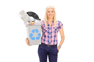 Girl holding recycle bin full of old accessories