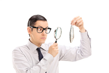 Man examining a fish through a magnifying glass
