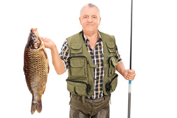 Mature fisherman holding big fish and fishing rod