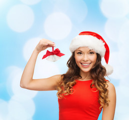 smiling woman in santa helper hat and jingle bells