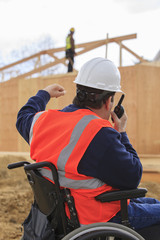 Construction engineer with spinal cord injury talking on radio