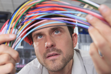 Network engineer examining multi color fiber and copper cables