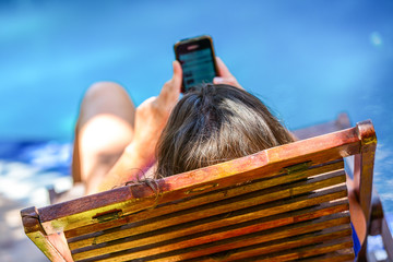 woman texting on her mobile phone while relaxing at the pool