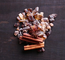 Reed sugar and spices on wooden background
