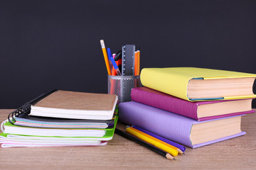 School supplies on table on dark background