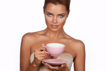 Young beautiful woman drink tea or coffee on a white background