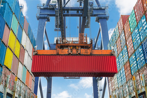 Leinwanddruck Bild Shore crane lifts container during cargo operation in port