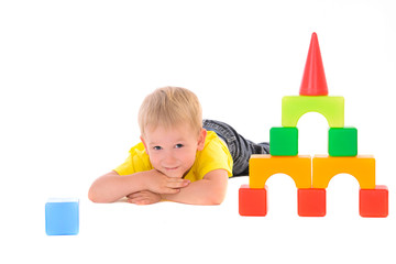 boy lying near toy building of colored cubes