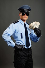 Policeman in uniform shows you money on gray background