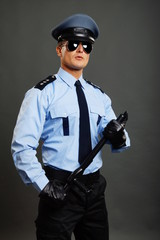Young policeman in uniform poses with nightstick