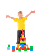 child builds a building of colored cubes
