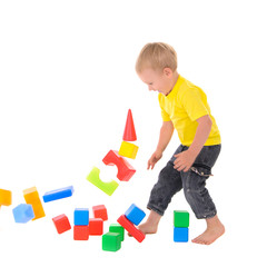 boy destroys toy building of colored cubes