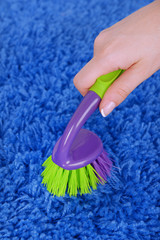Cleaning carpet with brush close up