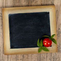 Tomato and Basil on black chalkboard. Selective focus.