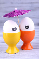 Pair of eggs in egg cups on grey wooden background