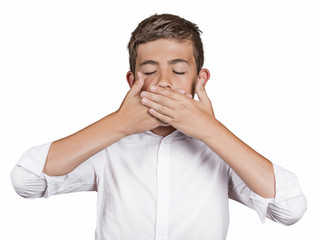 Boy covering mouth with hands won't talk. Speak no evil