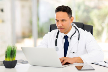 mid age medical doctor using laptop