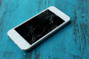 Modern mobile phone with broken screen on wooden background